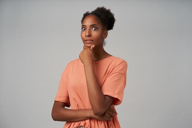 Giovane donna castana dalla pelle scura stupita che tiene la mano alzata sul mento e arrotondando con sorpresa i suoi occhi marroni, in piedi sul grigio
