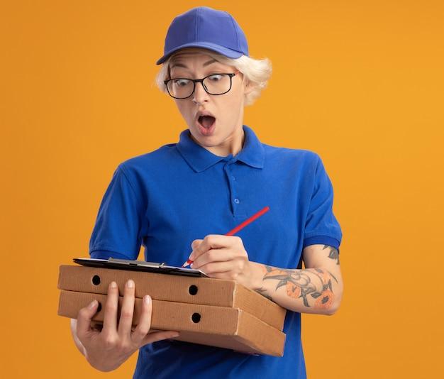 Stupita giovane donna delle consegne in uniforme blu e berretto con gli occhiali in possesso di scatole per pizza e appunti con pagine vuote che scrivono qualcosa con la matita sul muro arancione