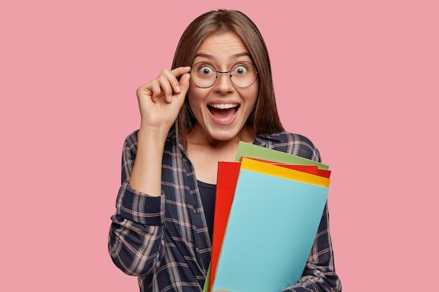La giovane ragazza europea stupita apre la bocca per lo stupore, tiene la mano sul bordo degli occhiali