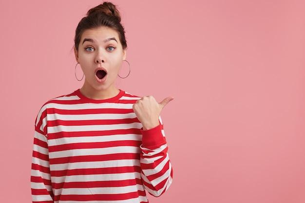 Giovane femmina stupita con le lentiggini, indossa maniche lunghe a righe; apre ampiamente la bocca per l'eccitazione, fa cadere la mascella, attira l'attenzione, isolato su punti rosa della parete con il pollice a destra sullo spazio della copia.