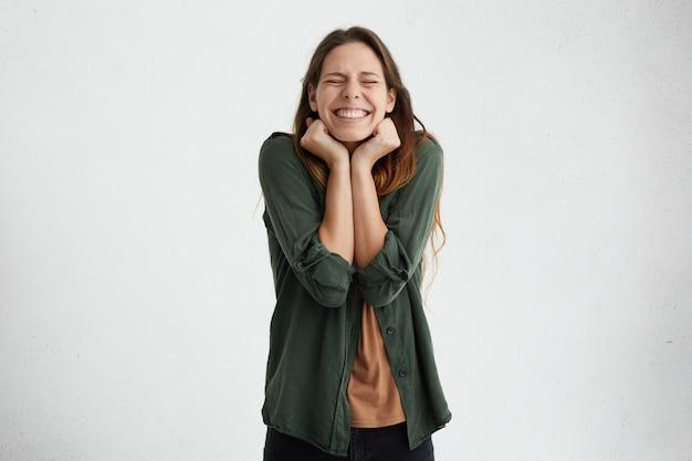 まっすぐな黒髪が目を閉じ、拳を握りしめている、笑顔が幸せな喜びで驚かれる若い女性