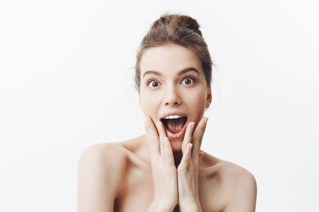 Amazed young good-looking european student girl with brown hair in bun hairstyle and naked shoulders, squeezing face with hands with surprised expression. beauty and health