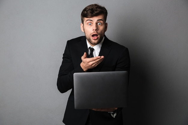 Amazed young guy in black suit holding laptop,