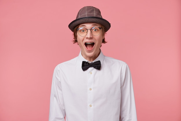 Amazed young guy in white shirt, hat and black bowtie wears glasses has braces, opened mouth widely in surprise, filled with emotion, isolated on pink background