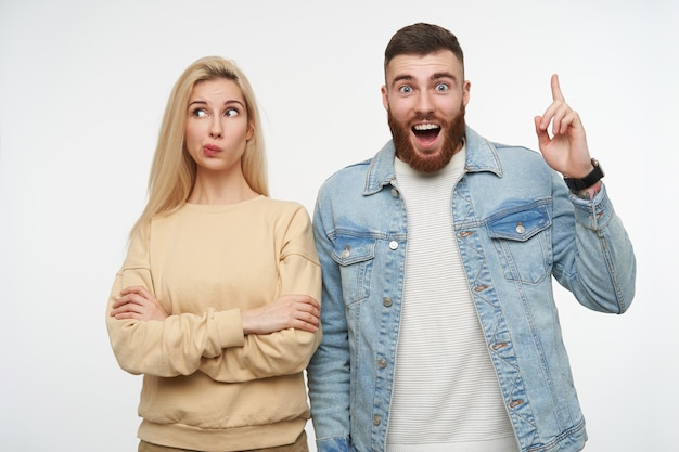 Amazed young handsome bearded brunette guy raising index finger and looking dazedly with wide eyes and mouth opened, posing on white with puzzled pretty blonde lady