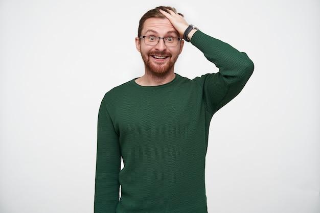 Изумленный молодой красивый бородатый мужчина в очках взъерошивает свои короткие каштановые волосы и удивленно округляет глаза, глядя в одиночестве