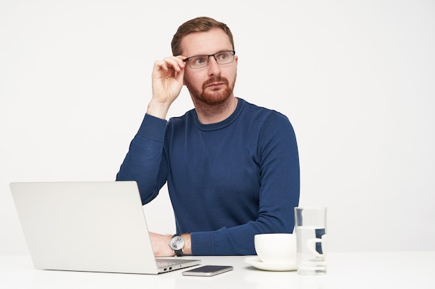 驚いた若いハンサムな金髪の男性は、驚いたことに脇を見て、白い背景の上に座って、彼の眼鏡に手を上げたまま、目を丸くします