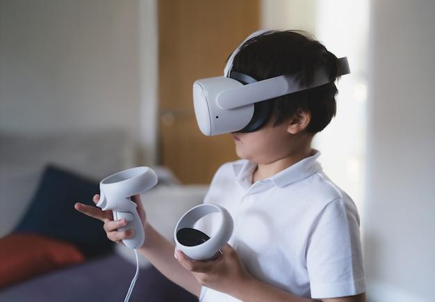 バーチャルリアリティゴーグルを身に着けている驚いた幼い子供。 vrヘッドセットで見てビデオゲームをプレイする感情的な少年。リビングルームで3dガジェットを体験している混血の少年の肖像画。