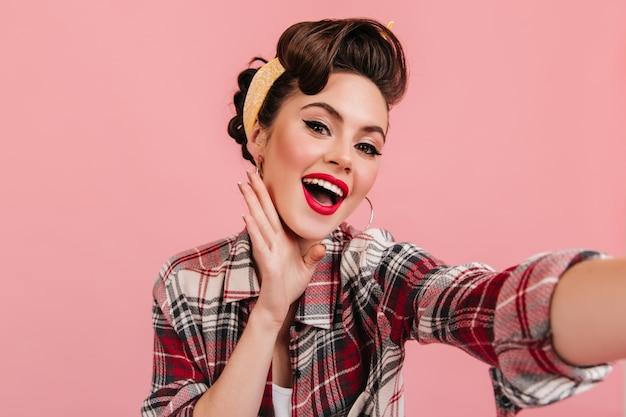 Giovane signora stupita in abbigliamento retrò che guarda l'obbiettivo. ragazza pinup accattivante prendendo selfie su sfondo rosa.