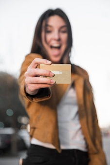 Amazed young lady with plastic card