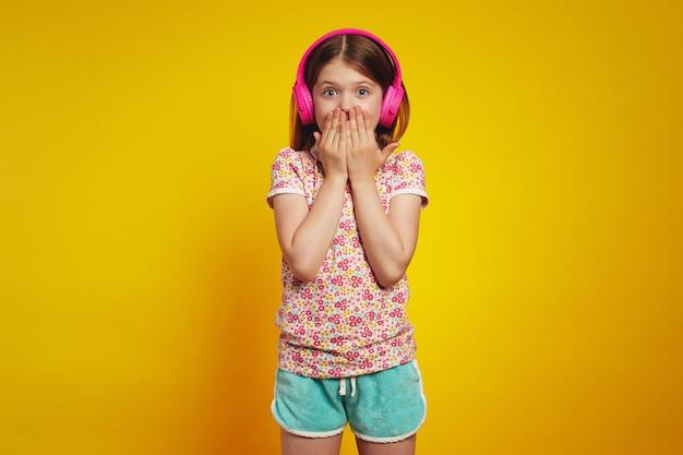 Пораженная маленькая девочка с наушниками на желтом фоне