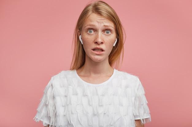 분홍색 배경 위에 포즈를 취하는 동안 우아한 옷을 입고 카메라를 혼란스럽게보고 그녀의 이빨을 보여주는 동안 폭시 머리 주름이 이마를 가진 놀란 젊은 사랑스러운 아가씨