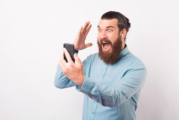 Пораженный молодой хипстер мужского пола смотрит на телефон, который он держит в наушниках.
