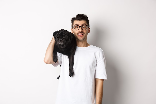 Amazed young man in glasses holding black pug on shoulder and staring at camera impressed. dog owner posing with cute puppy near white background.