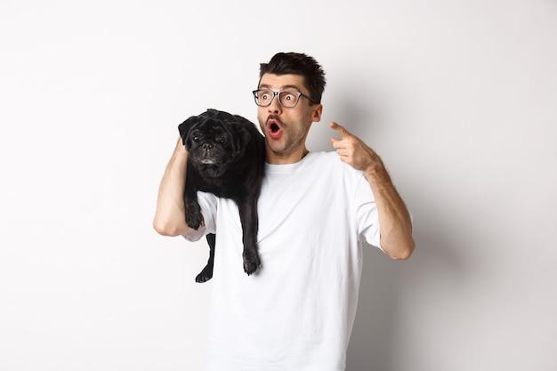 Giovane stupito che tiene in mano un simpatico cane nero sulla spalla, puntando il dito a sinistra all'offerta promozionale, fissando impressionato e senza parole, in piedi su sfondo bianco.