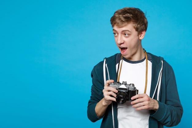 파란색 벽에 고립 된 레트로 빈티지 사진 카메라를 들고 옆으로 입 벌리고 찾고 캐주얼 옷에 놀란 된 젊은 남자. 사람들은 성실한 감정, 라이프 스타일 개념.