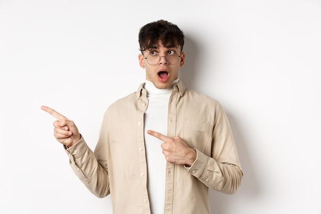 眼鏡をかけた驚いた若い男は、すごいことを言って、素晴らしいプロモーションのオファーを指差して左を見て、不信と印象的な顔、白い背景で見つめます。