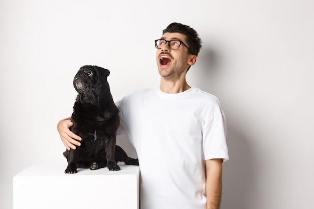 Пораженный молодой человек в очках обнимает свою собаку, владельца домашнего животного и мопса, глядя на промо-предложение в верхнем левом углу, стоя на белом фоне.