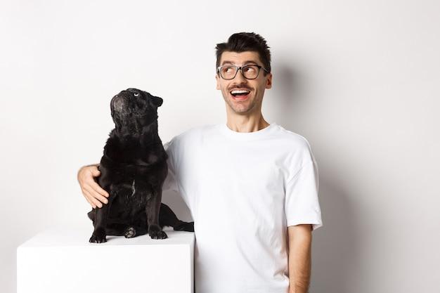 白い背景の上に立って、彼の犬、ペットの飼い主、左上隅のプロモーションオファーを見つめているパグを抱き締める眼鏡をかけた驚いた若い男。