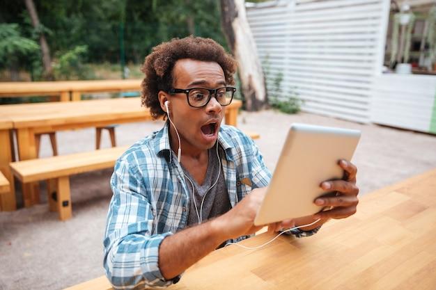 Пораженный молодой человек в очках с планшетом сидит и кричит на открытом воздухе