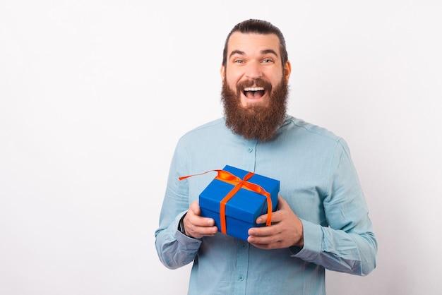 Пораженный молодой человек держит подарочную коробку, улыбаясь в камеру.