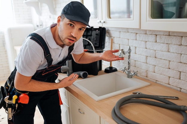Amazed young man look on camera and point on sink in kitchen