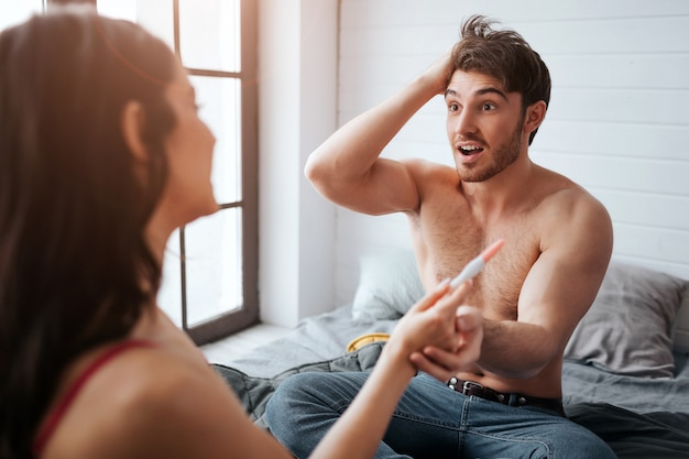 Amazed young man look at woman and hold her hand with pregnancy test. he is happy. they sit on bed. happy woman look at him.