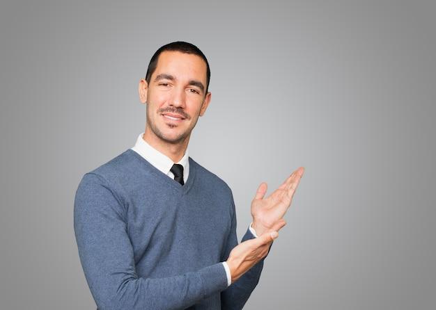 Пораженный молодой человек делает приветственный жест