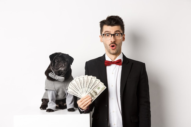 Amazed young man in party suit, standing near cute black pug dog in costume