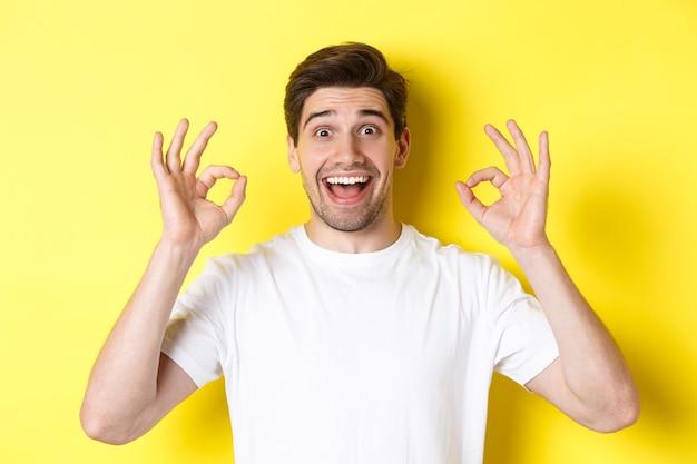 大丈夫な兆候を示し、笑顔で、黄色の背景の上に立って、何か良いものを勧めて、満足している驚いた若い男。