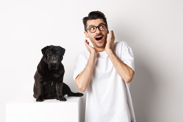 Пораженный молодой человек, стоящий с милым черным щенком, глядя в правый верхний угол, удивлен и взволнован, стоя рядом с мопсом на белом фоне.