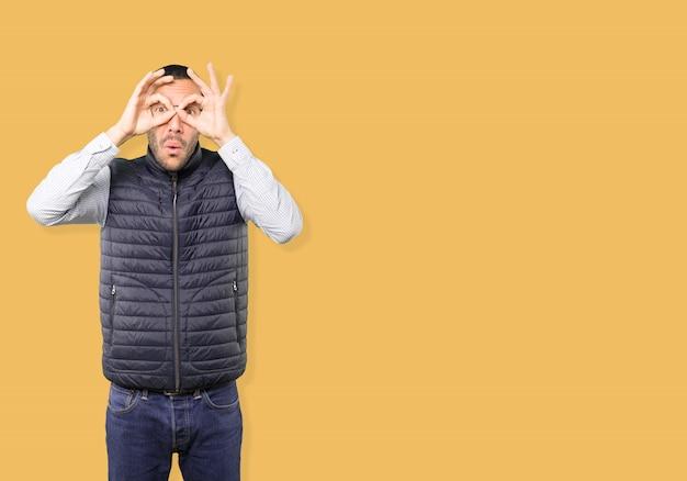 쌍안경처럼 그의 손을 사용하여 놀란 젊은이