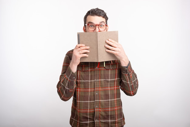 Amazed young man wearing glasses on white spaces is covering his face with an opened book. reading time.