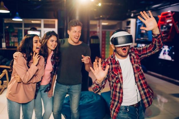 プレイルームでvrメガネと手を振る若い男を驚かせた。彼の友達は幸せそうで興奮しています。彼らは後ろに立っています。