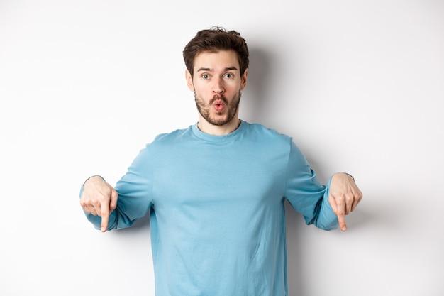 Пораженный молодой человек с бородой, стоящий в повседневной синей рубашке, говоря «вау» и указывая вниз, смотри сюда жест, стоящий на белом фоне.