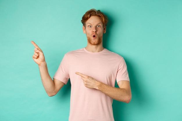赤い髪とあごひげを生やした驚愕の青年、あえぎ驚いて、左上隅を指してプロモーションを表示し、広告をチェックし、ターコイズブルーの背景の上に立っています。