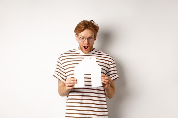 Amazed young man with red hair, staring at paper house cutout with excitement, standing over white background.
