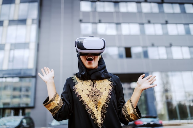 Amazed young muslim woman in traditional wear standing outdoors and using vr goggles. millennial generation.