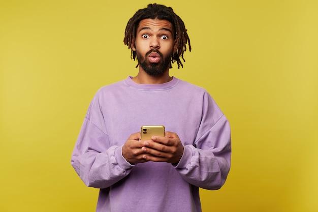 驚いた若いかなり茶色の髪のひげを生やした男は、カメラを驚いて見ながら、目を丸くして、スマートフォンを上げた手で黄色の背景の上にポーズをとっています。