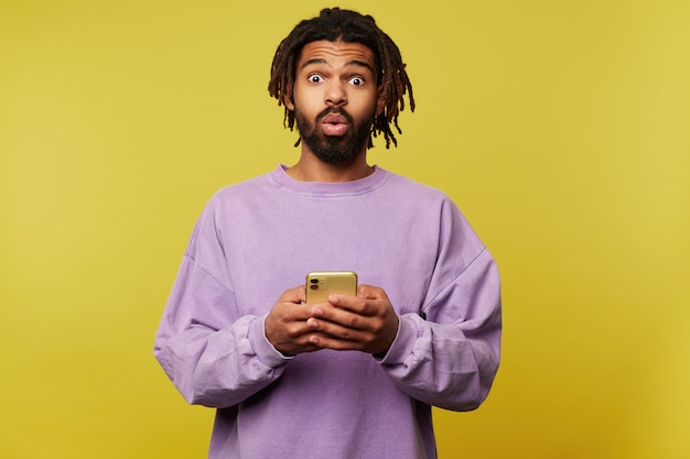 Amazed young pretty brown haired bearded guy with dark skin rounding his eyes while looking surprisedly at camera, posing over yellow background with smartphone in raised hands