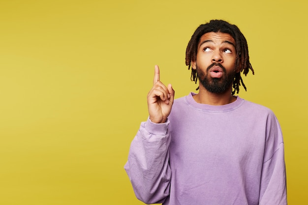 Amazed young pretty dark skinned brunette guy with dreadlocks looking surprisedly upwards and keeping forefinger raised, standing against yellow background