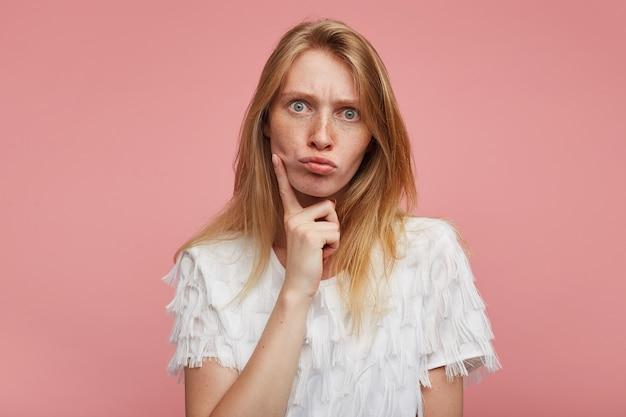 Giovane bella femmina stupita con i capelli voluminosi che arrotondano gli occhi grigio-verdi mentre guarda la telecamera con le labbra imbronciate, tenendo il dito indice sulla guancia mentre posa su sfondo rosa