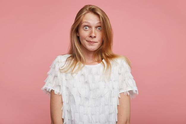 Stupito giovane donna graziosa rossa con acconciatura casual che arrotonda i suoi occhi grigio-verdi mentre guarda sorpreso alla fotocamera, isolata su sfondo rosa con le mani verso il basso