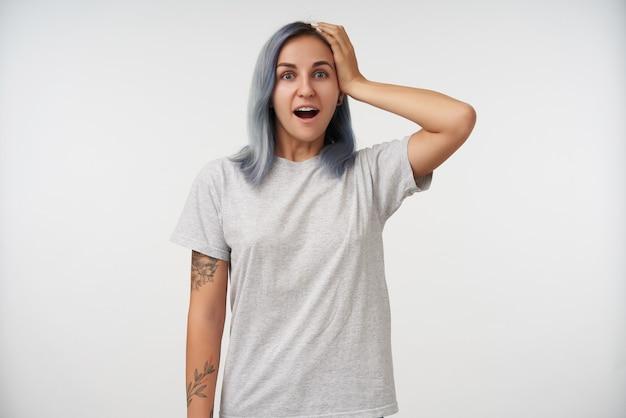Giovane femmina piuttosto tatuata stupita con capelli blu corti che tiene la mano alzata sulla sua testa mentre guarda sorpresa, in piedi su bianco