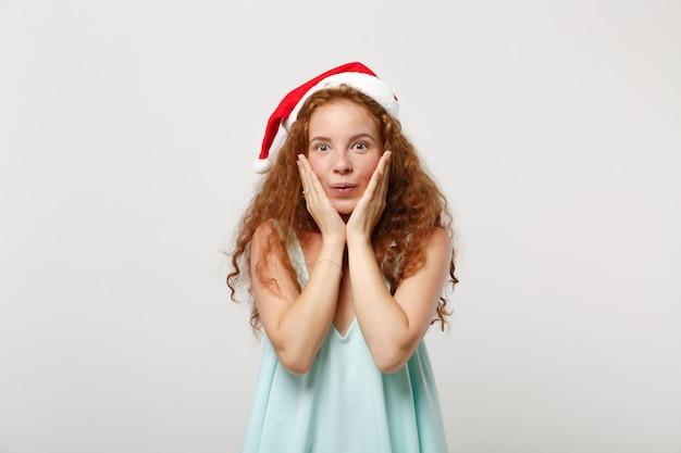 Пораженная молодая рыжая девушка санта в легкой одежде, рождественская шапка на белом фоне в студии. с новым годом 2020 праздник праздник концепции. копируйте пространство для копирования. положить руки на щеки.