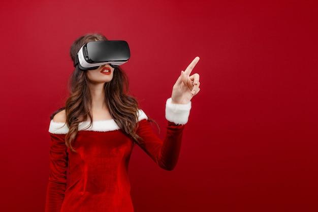 빨간색 배경에 격리된 손을 옆으로 가리키는 헤드셋을 보고 크리스마스 드레스를 입은 젊은 산타 소녀