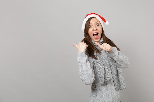 灰色のセーターのスカーフのクリスマスの帽子をかぶった若いサンタの女の子を驚かせ、口を大きく開いたまま、灰色の背景に孤立して叫んで親指を脇に向けます。明けましておめでとうございます2019お祝いホリデーパーティーのコンセプト。