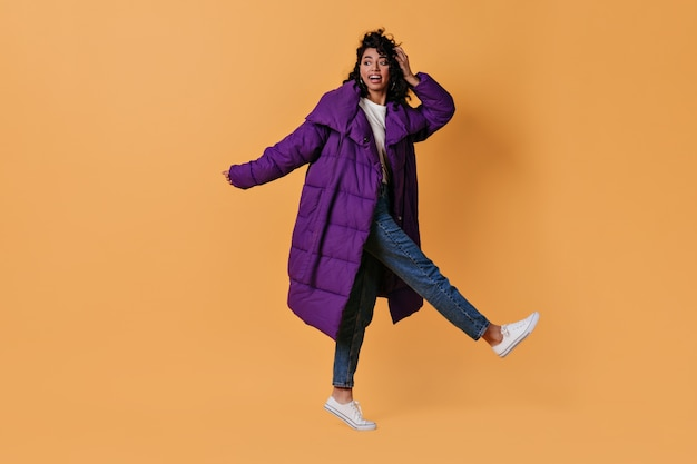 Amazed young woman in down jacket standing on one leg