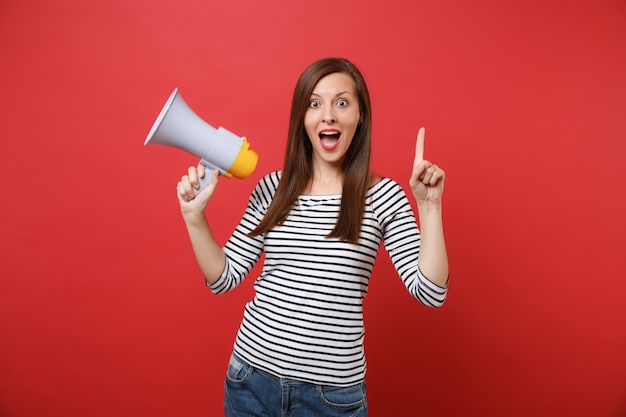 Amazed young woman holding megaphone keeping mouth wide open looking surprised pointing index finger up isolated on red wall background. people sincere emotions, lifestyle concept. mock up copy space.