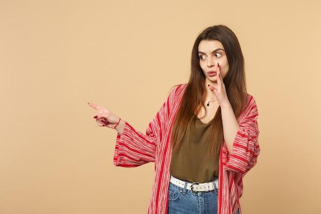 パステルベージュの背景で隔離された人差し指を脇に向けて、彼女の手の後ろに秘密をささやくカジュアルな服を着て驚いた若い女性。人々の誠実な感情、ライフスタイルのコンセプト。コピースペースをモックアップします。